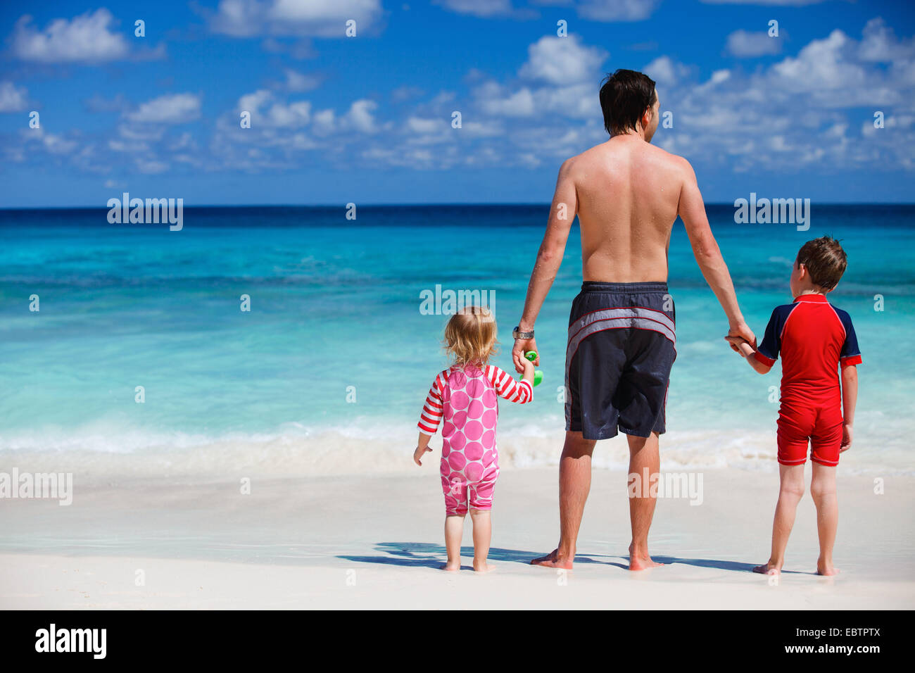father standing with his two small kids at tropical beach - Stock Image