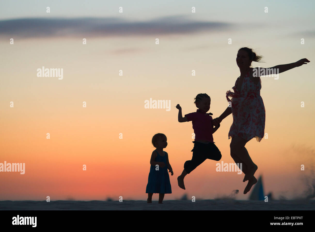 silhouettes of mother and two children jumping on beach at sunset - Stock Image