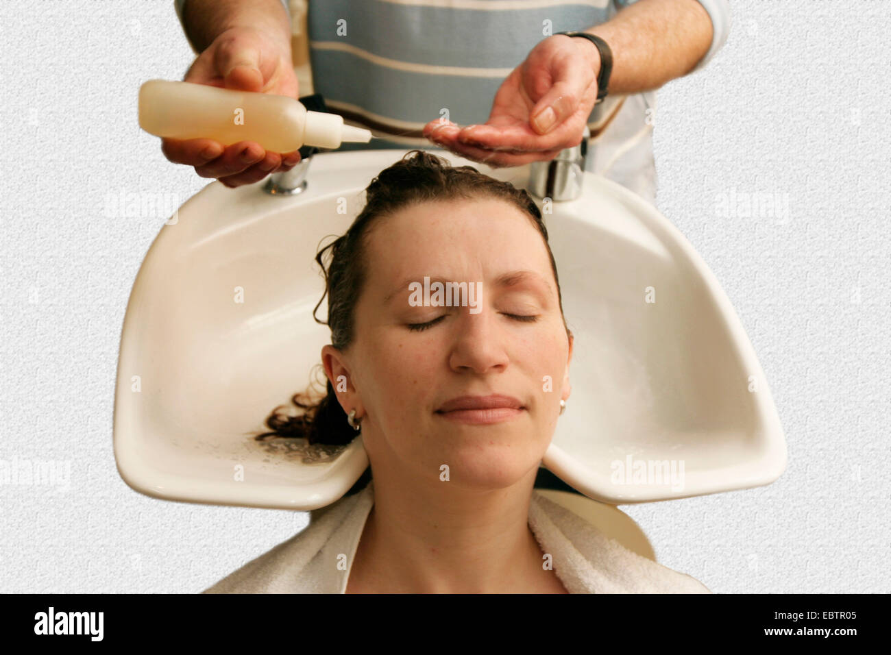 hairdresser washing hairs of a woman - Stock Image