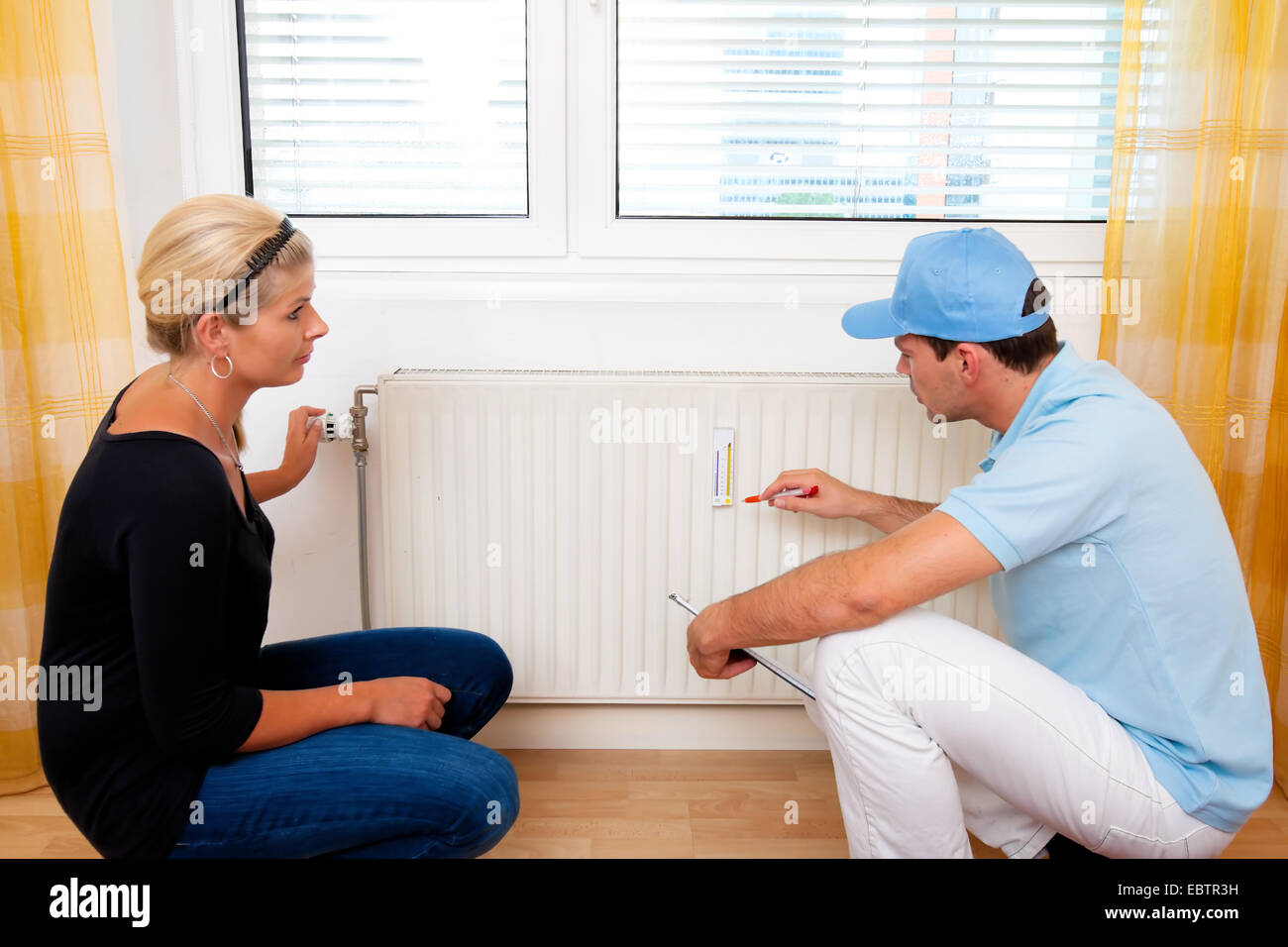 plumber crouching at a heater with a woman in her flat - Stock Image