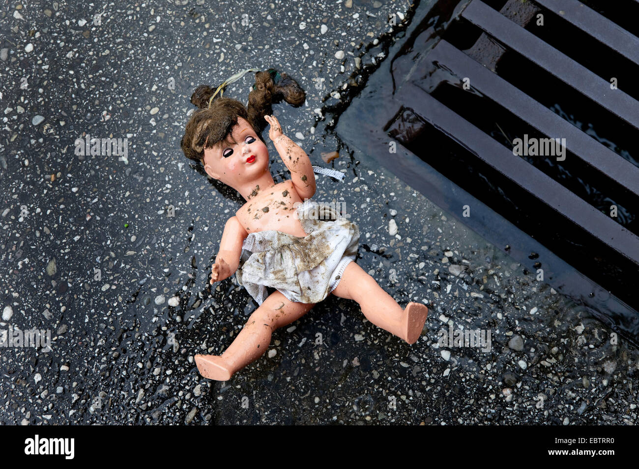 doll lying on a street, symbol of mistreatment and abuse of children - Stock Image