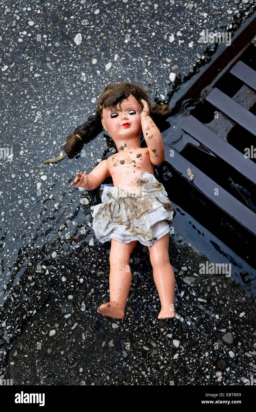 dolly lying on a street, symbol of mistreatment and abuse of children - Stock Image