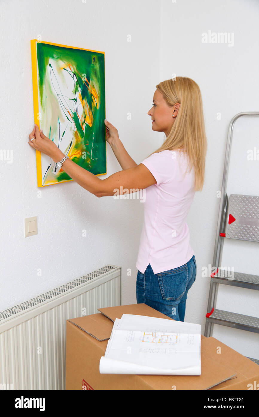 young woman hanging up a picture in her new flat with a moving box standing beside her Stock Photo