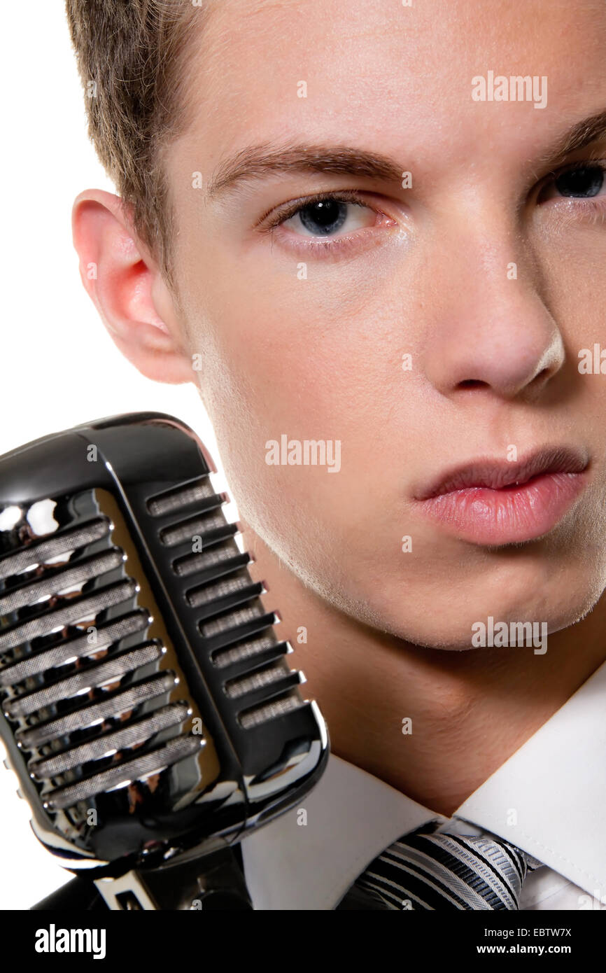young singer with retro microphone sings karaoke - Stock Image