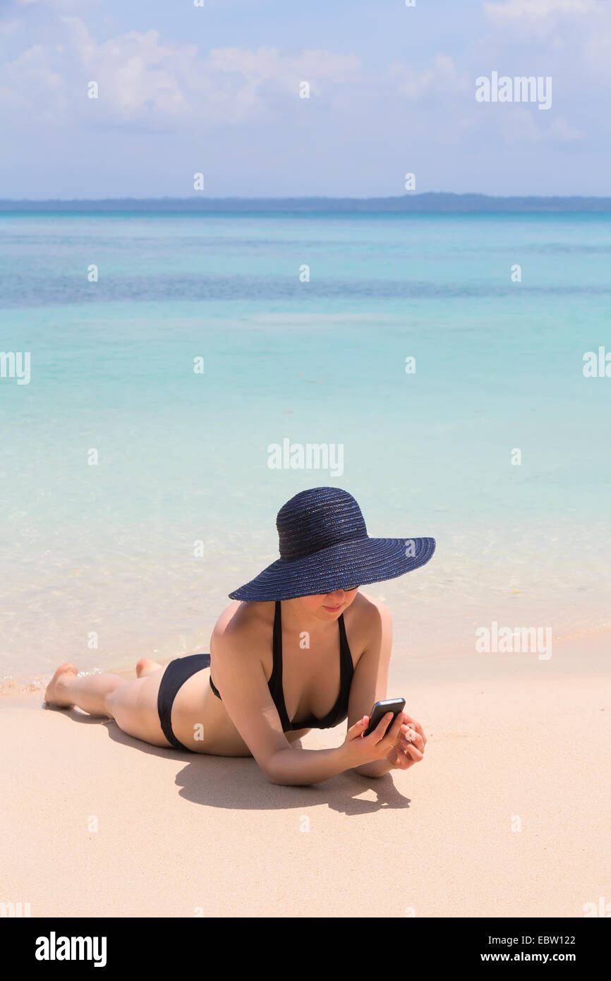 Woman looking at mobile phone on the beach, archipelago Bocas del Toro, Panama Stock Photo