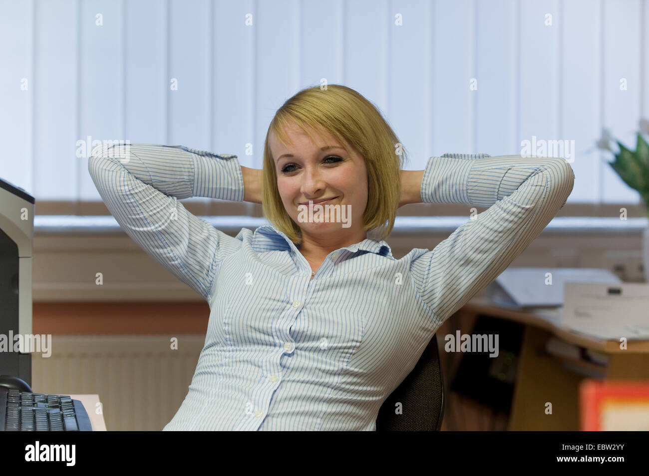 young secretary settling back at her workplace in the office - Stock Image