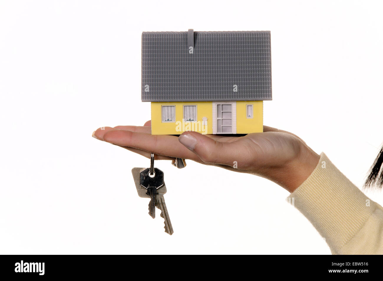 hand with miniatur model of a house and house keys Stock Photo