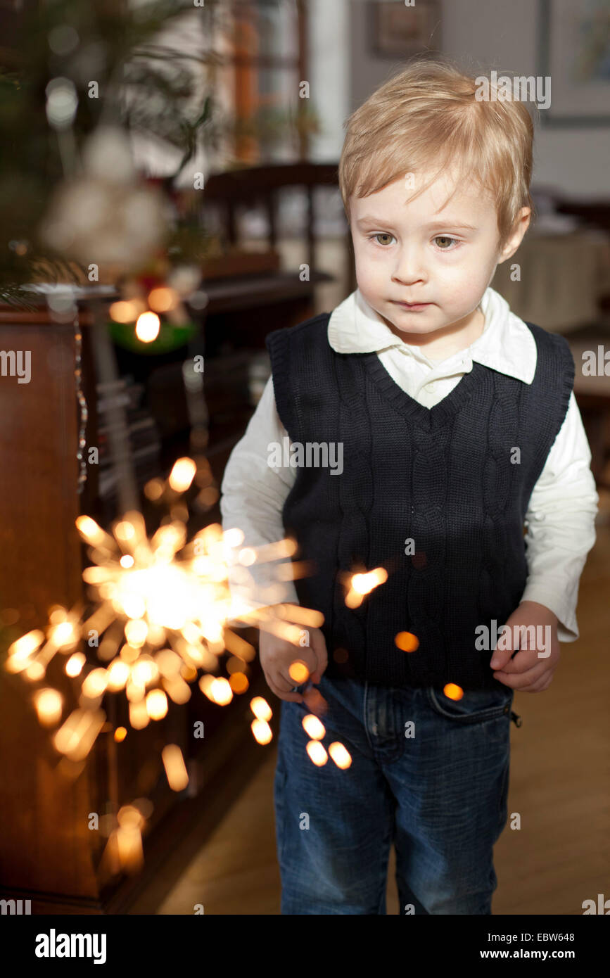 little boy standing in the living room watching a burning sparkler in hand Stock Photo