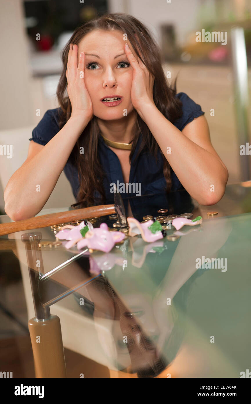 young woman sitting in front of a butchered piggy bank looking up desperately with the head in the hands - Stock Image