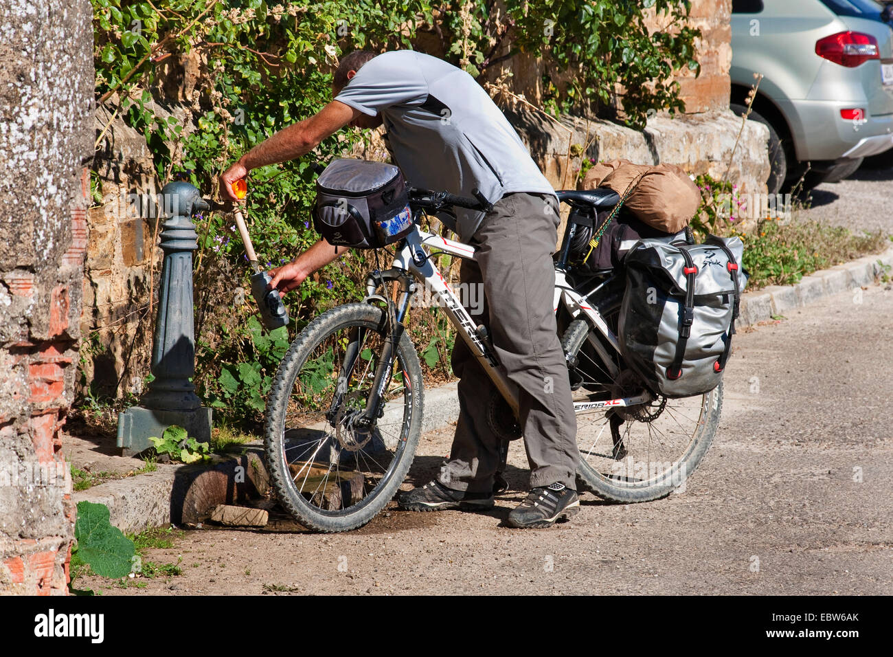 bicycle pilgrim filling up his waterbottle, Spain, Kastilien & Le�n, Leon, El Ganso - Stock Image