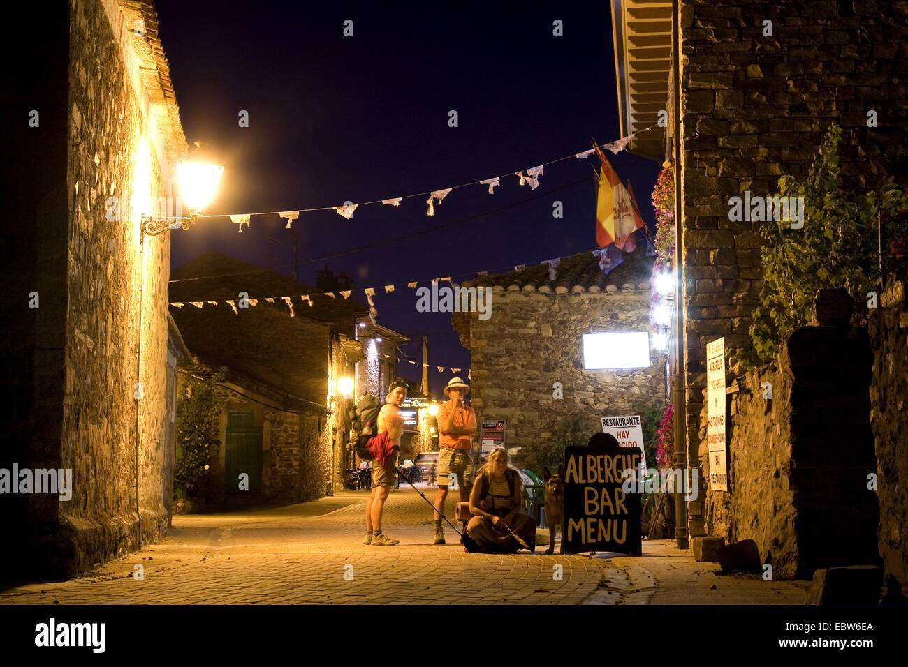 group of young pilgrims on Way of St. James arriving at the pilgrim's hostel at night, Spain, Kastilien und - Stock Image