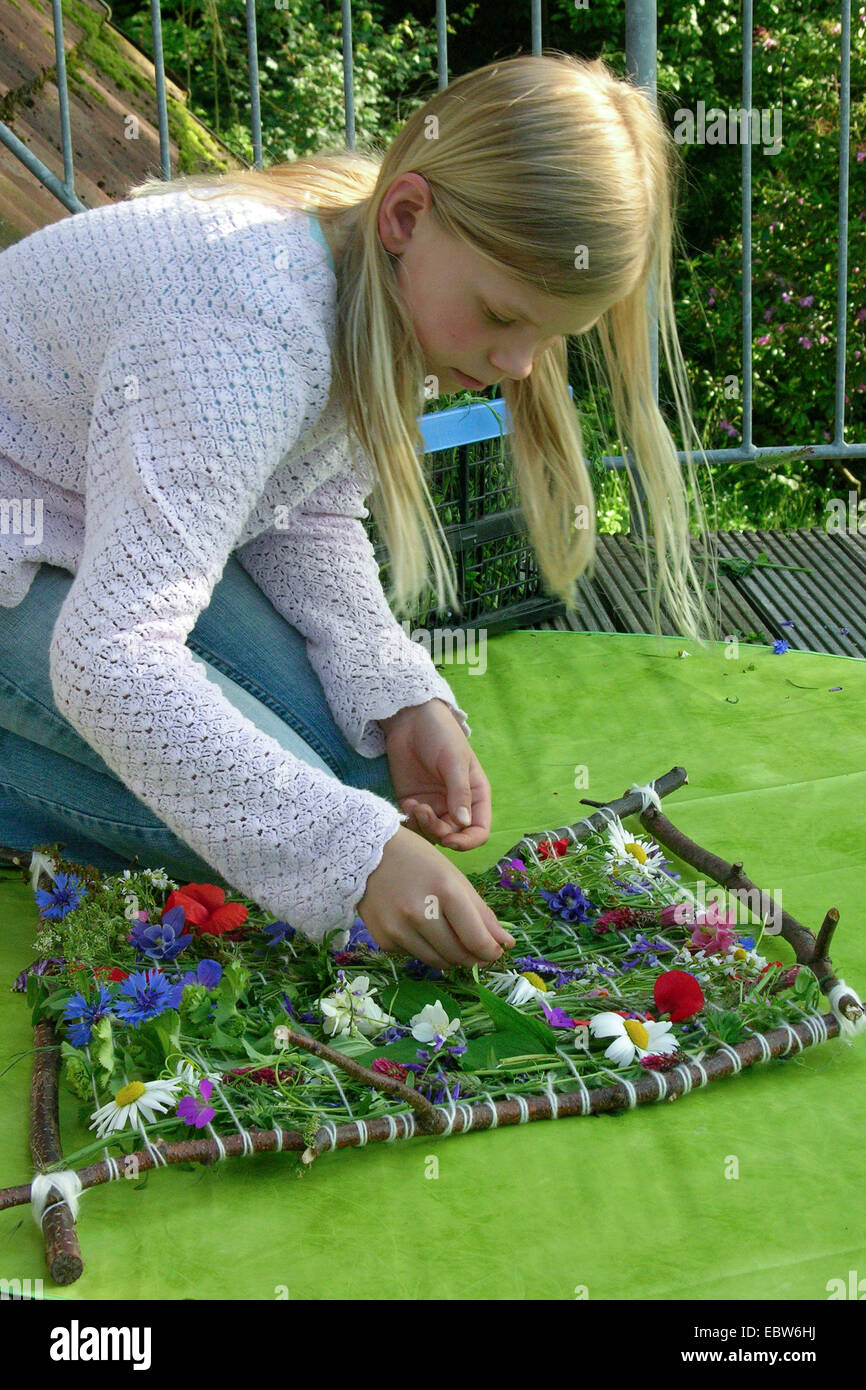 girl weaving a colourful floral decoration, Germany - Stock Image