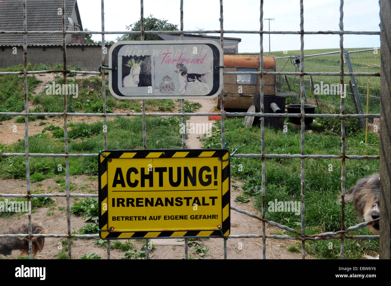 , warning sign 'caution! madhouse' at seedy garden,  , - Stock Image
