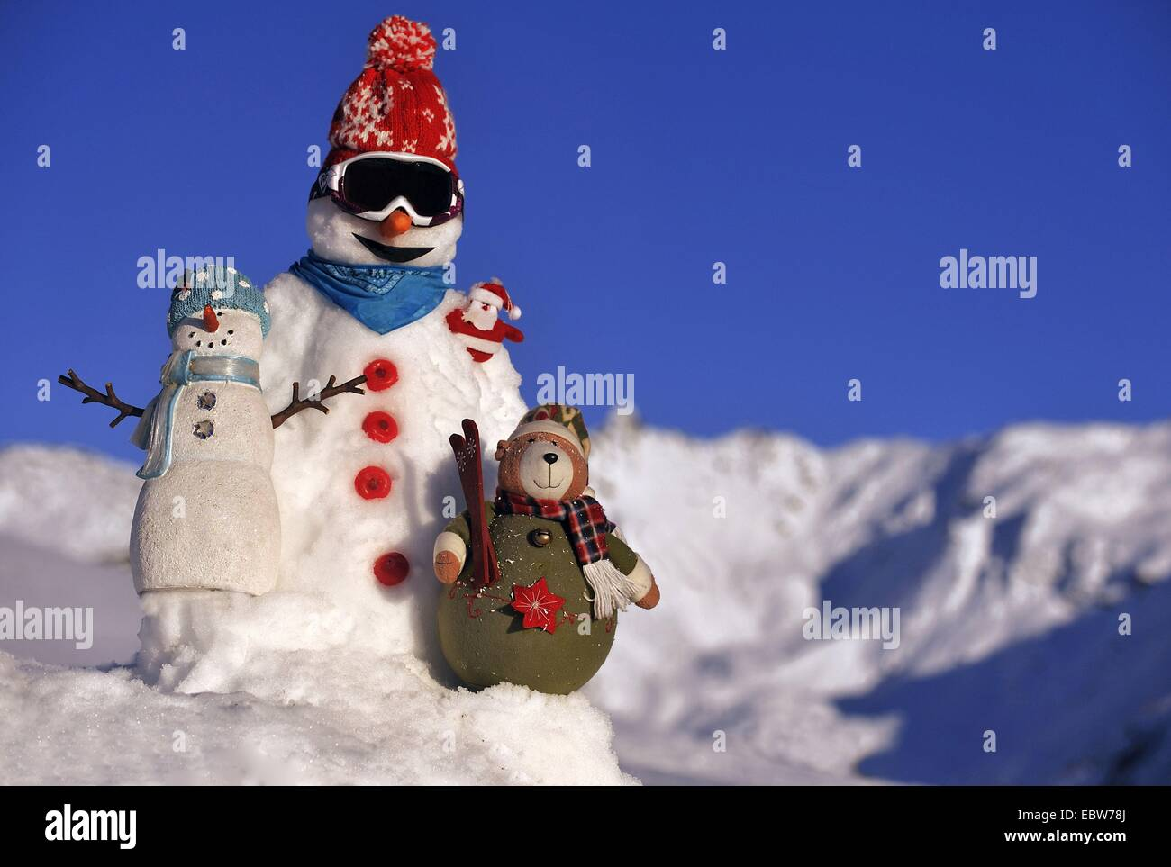 snowman with bobble hat and ski goggles in front of snow covered mountain range and blue sky, France - Stock Image