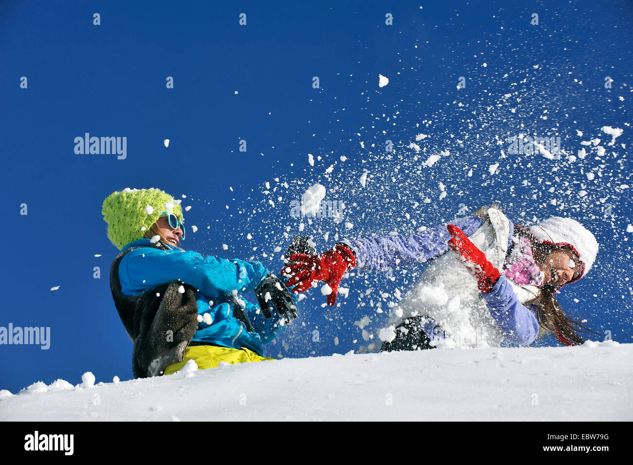 two young girls frolicly fighting in the snow, France - Stock Image