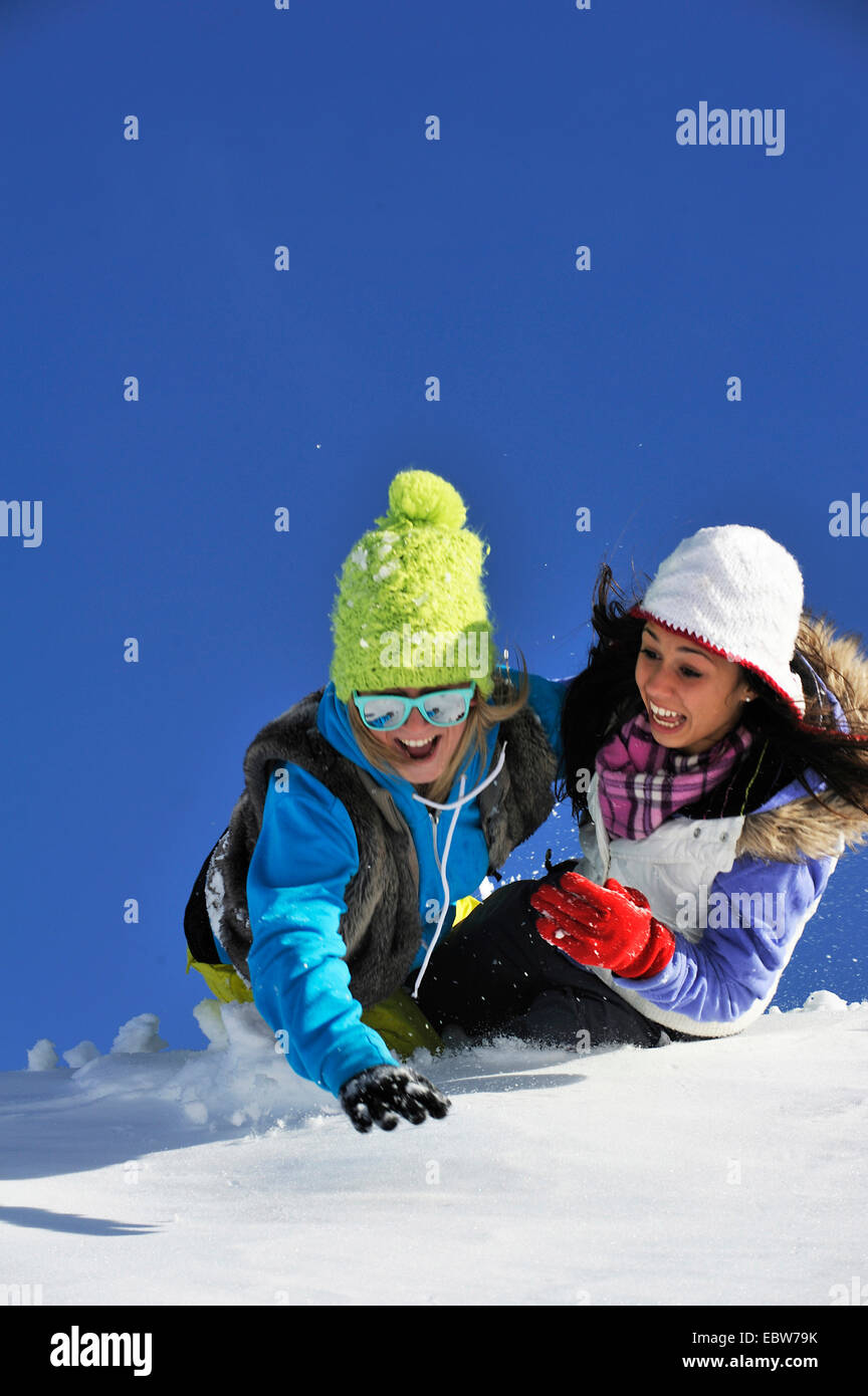 two young girls frolicly fooling around in the snow, France - Stock Image