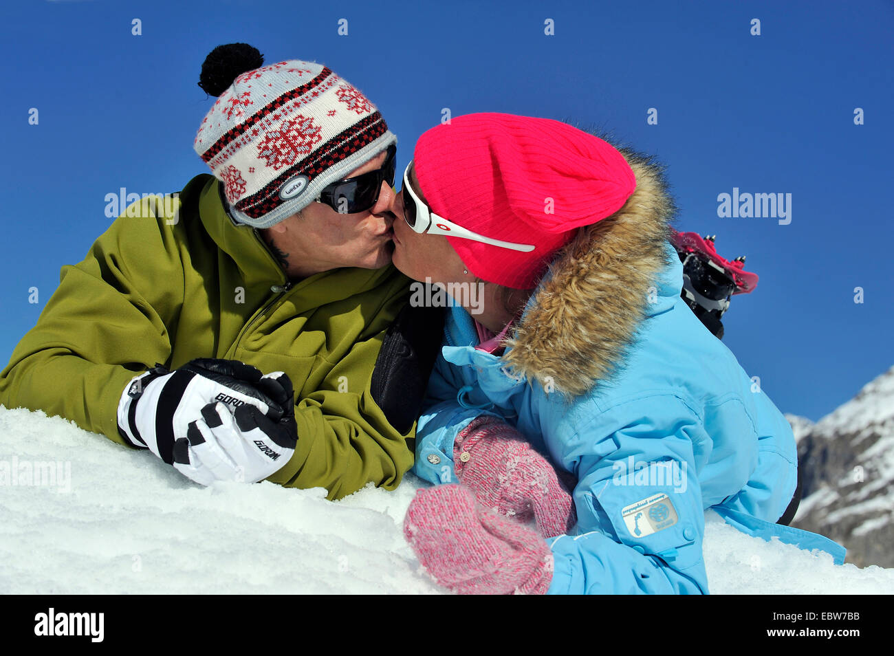 couple on winter vacation lying in the snow side by side on their bellies kissing each other, France - Stock Image