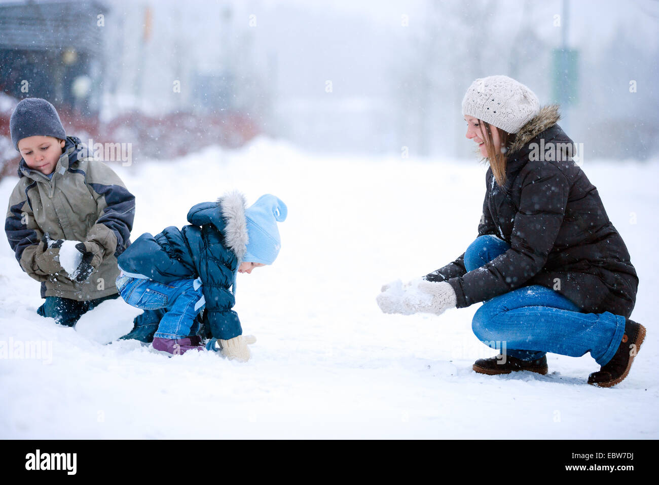 a mother playing with her two little children in snow - Stock Image