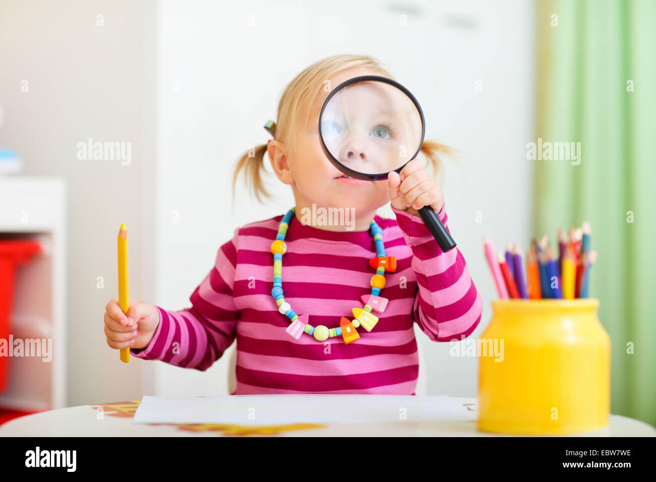 a little girl looking through a loupe - Stock Image