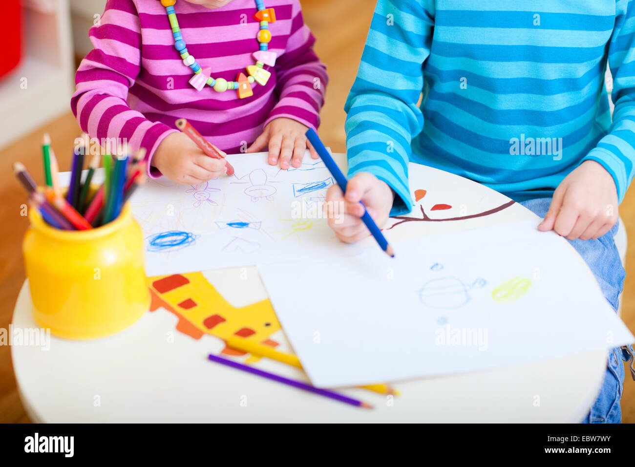 two little children drawing with crayons - Stock Image