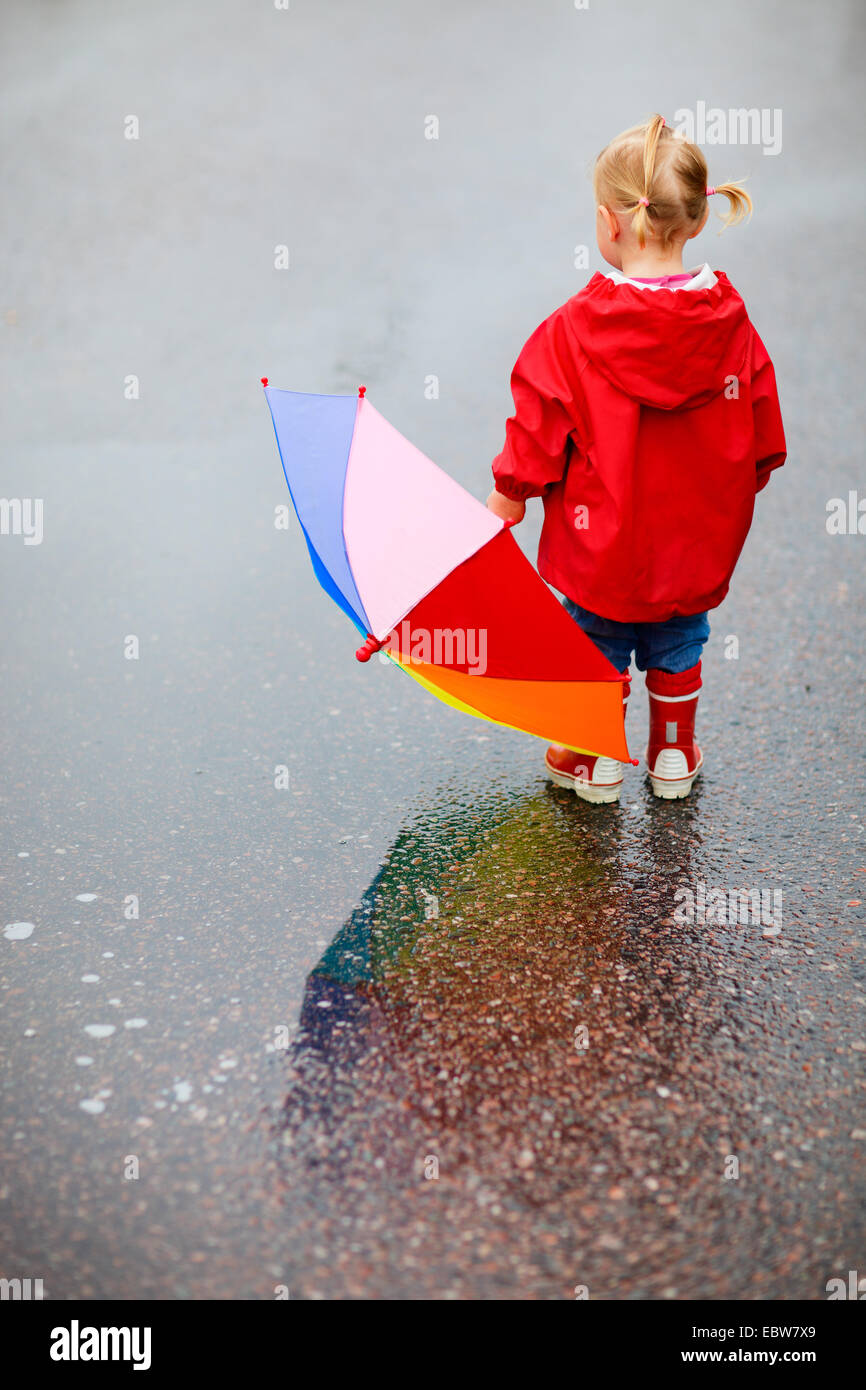 view from behind a little girl with an umbrella Stock Photo
