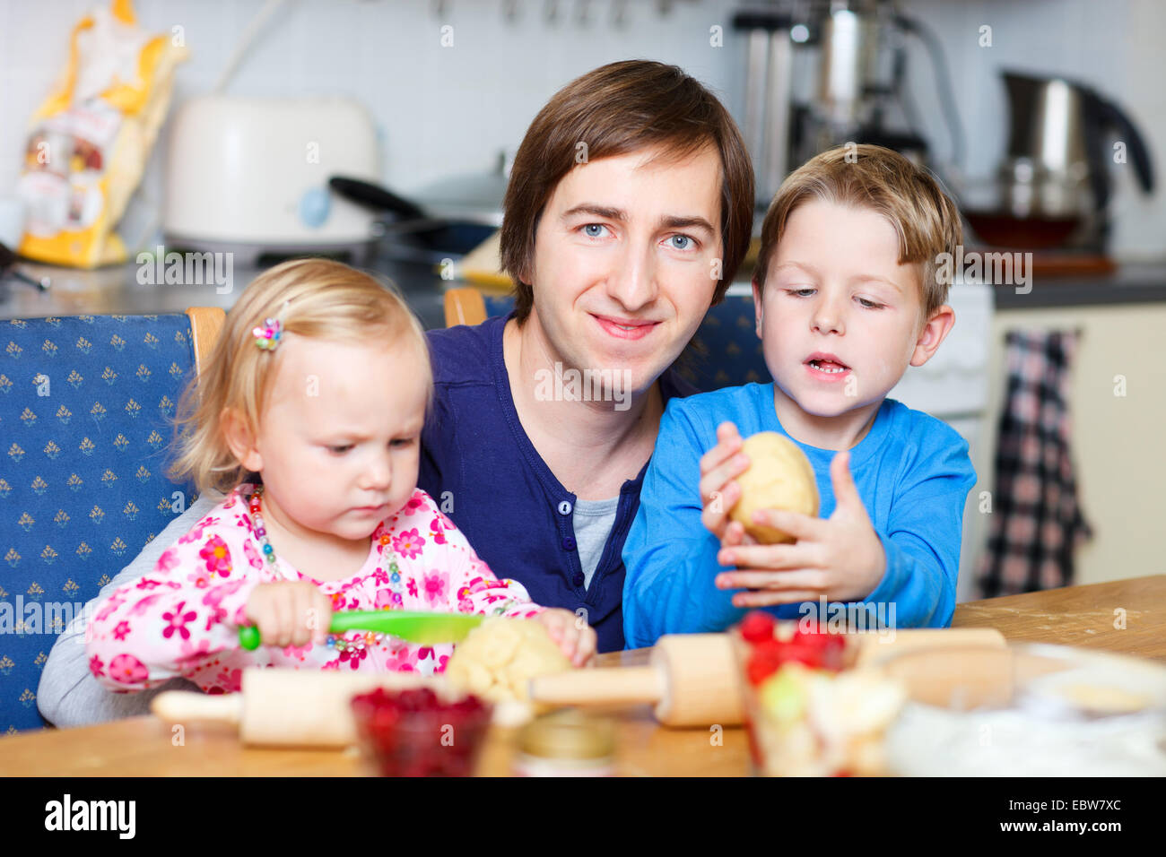 father baking biscuits with his daughter and his son - Stock Image
