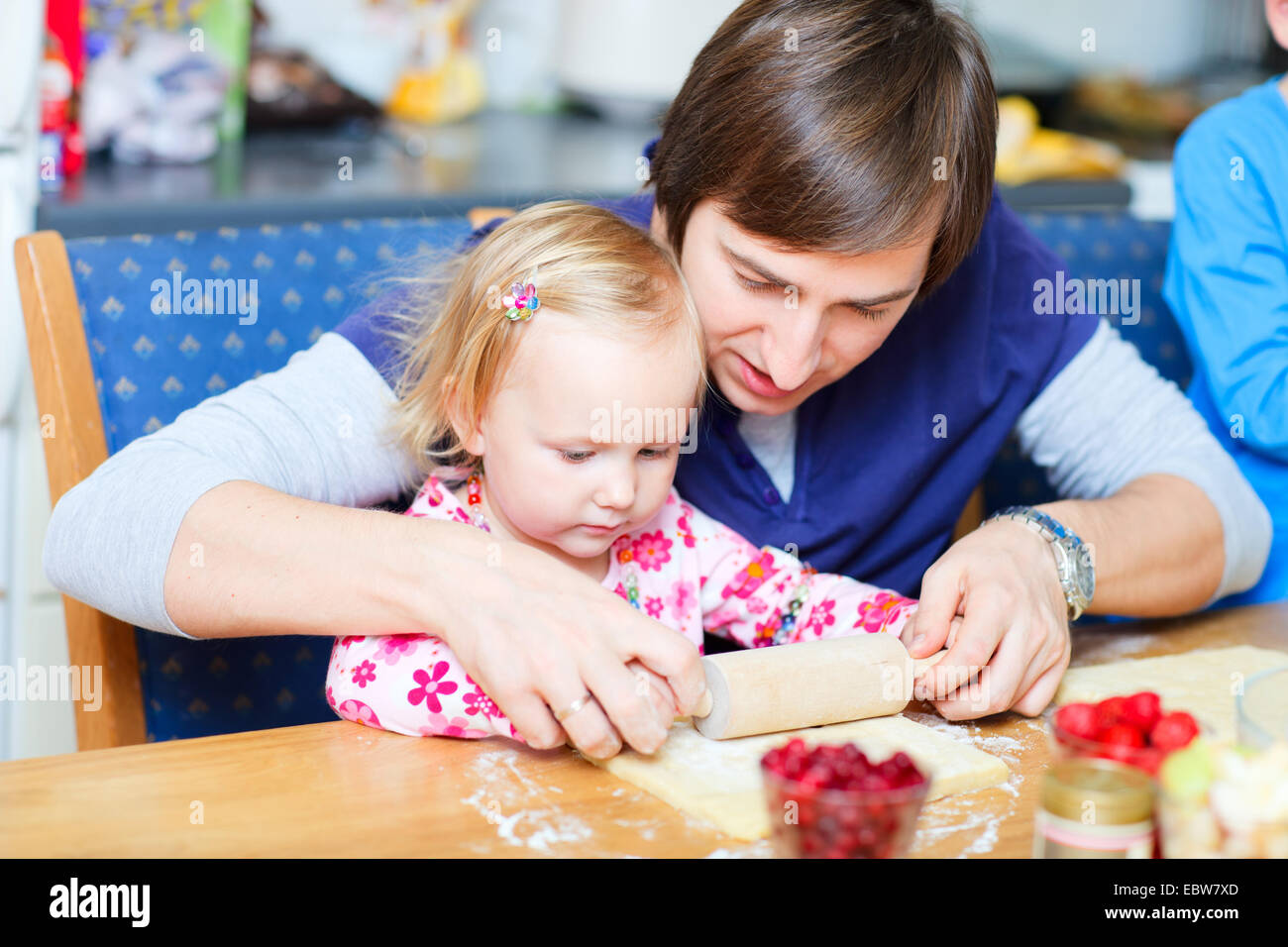 father baking biscuits with his little daughter - Stock Image