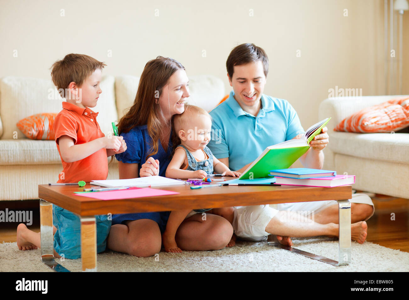 family with two children reading and painting in living room - Stock Image