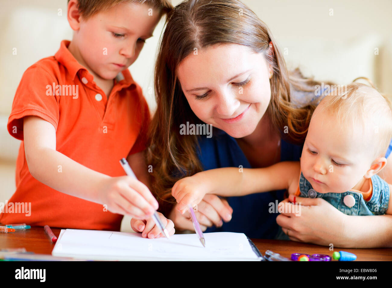 a young mother painting with her two children - Stock Image