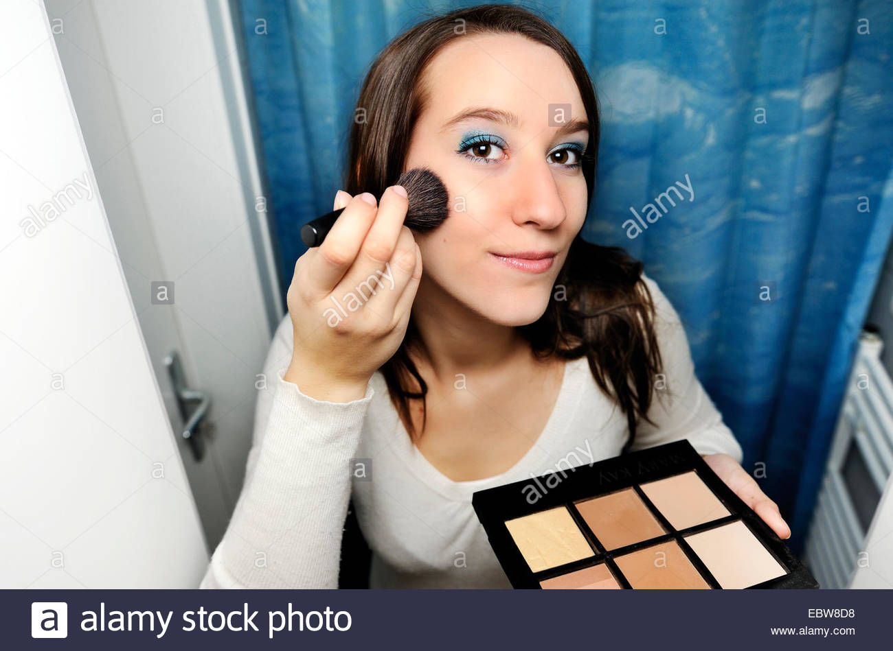 young woman putting on makeup Stock Photo