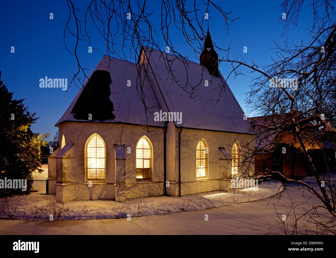 illuminated chappel of Herten castle in winter at blue our, Germany, North Rhine-Westphalia, Ruhr Area, Herten - Stock Image
