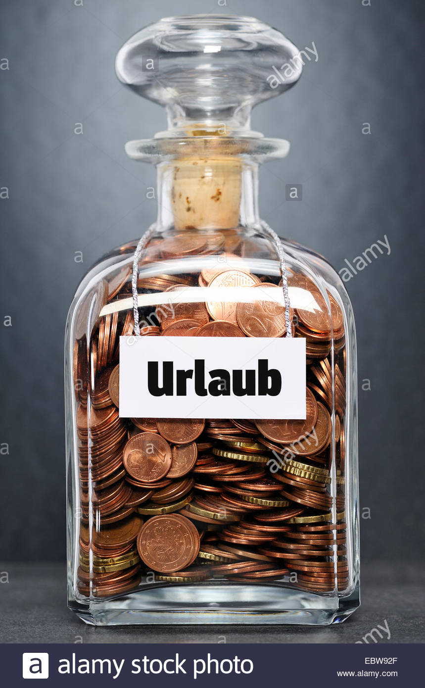glass bottle with Euro-coins labelled 'holidays' - 'Urlaub' - Stock Image