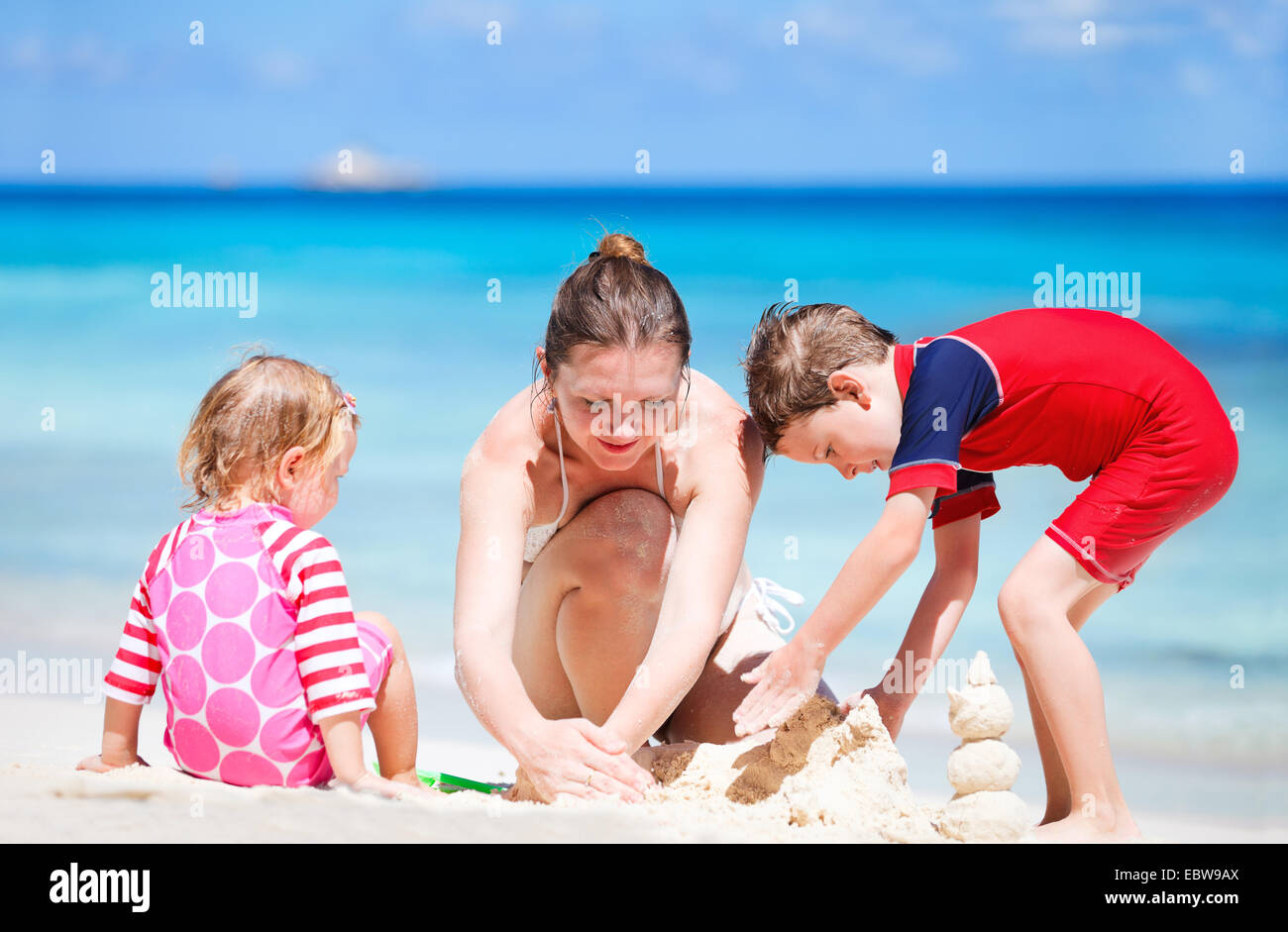 a young mother and her two children building a sand castle on sandy beach - Stock Image