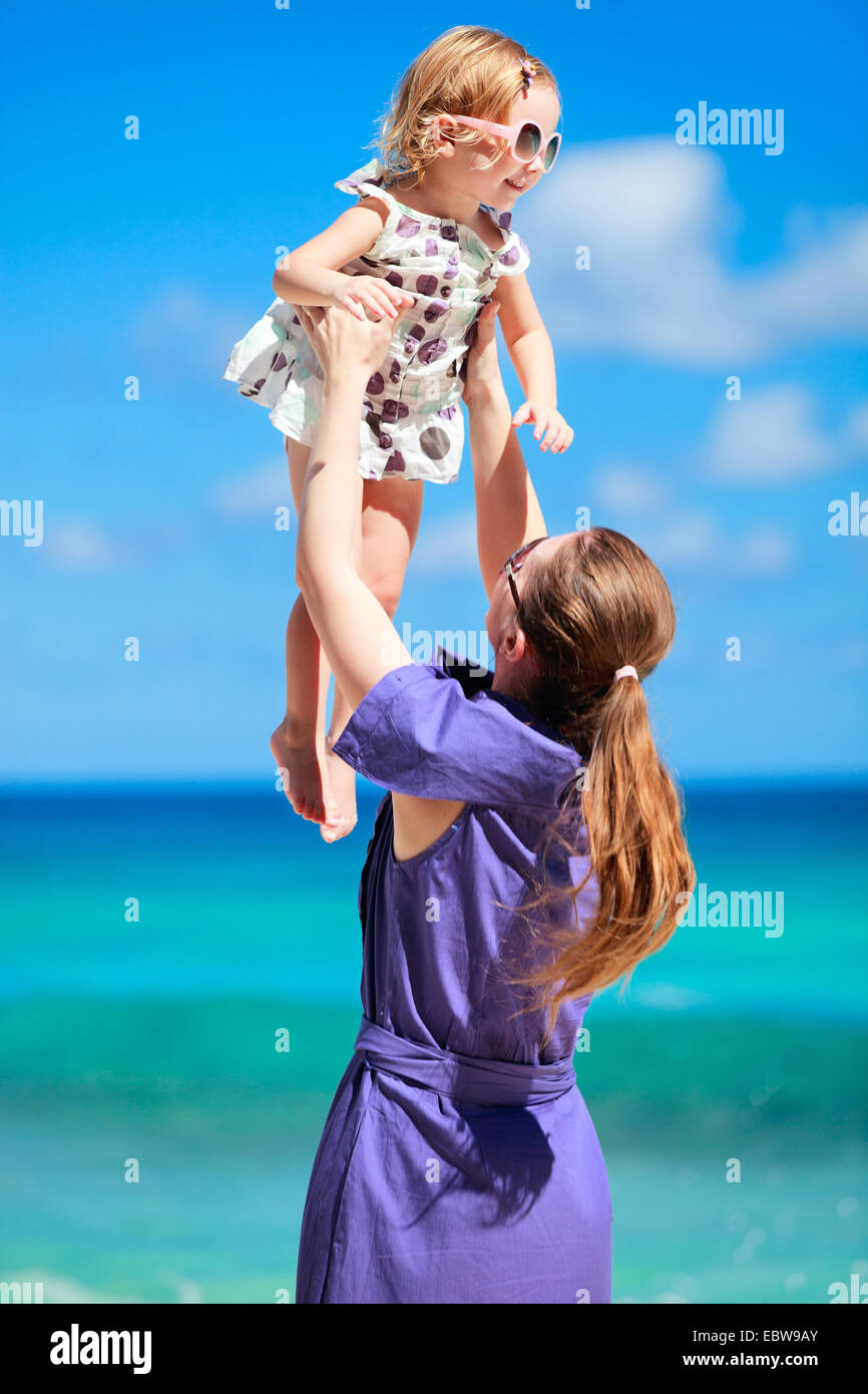 a young mother lifting up her little daughter on tropical beach - Stock Image