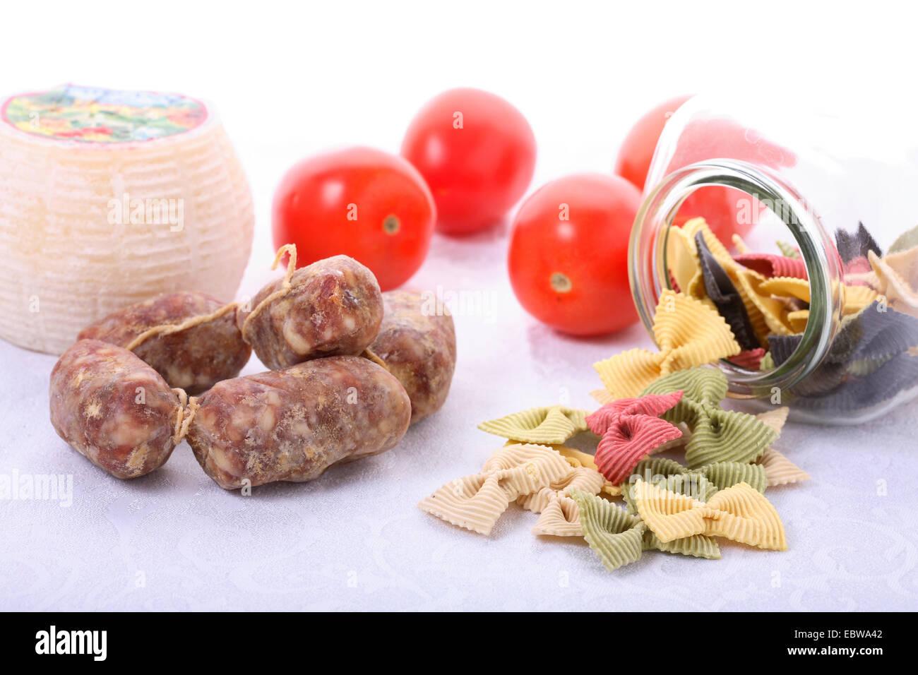 italian gastronomic specialties, salami, tomatoes and farfalle - Stock Image