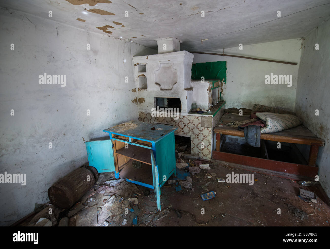 big stove with bedspace in old wooden cottage in abandoned Stechanka village, Chernobyl Exclusion Zone, Ukraine Stock Photo