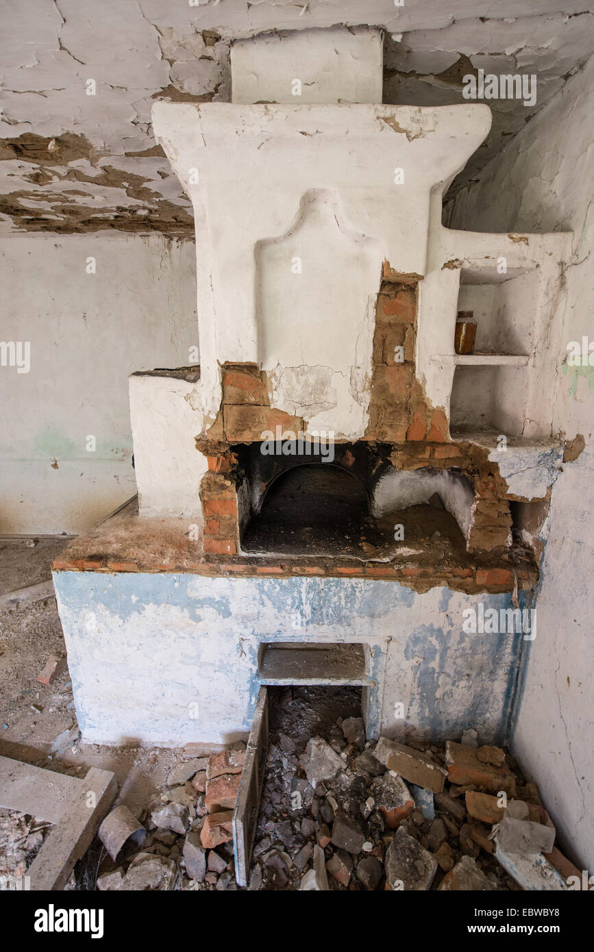 big stove in old wooden cottage in abandoned Stechanka village, Chernobyl Exclusion Zone, Ukraine - Stock Image