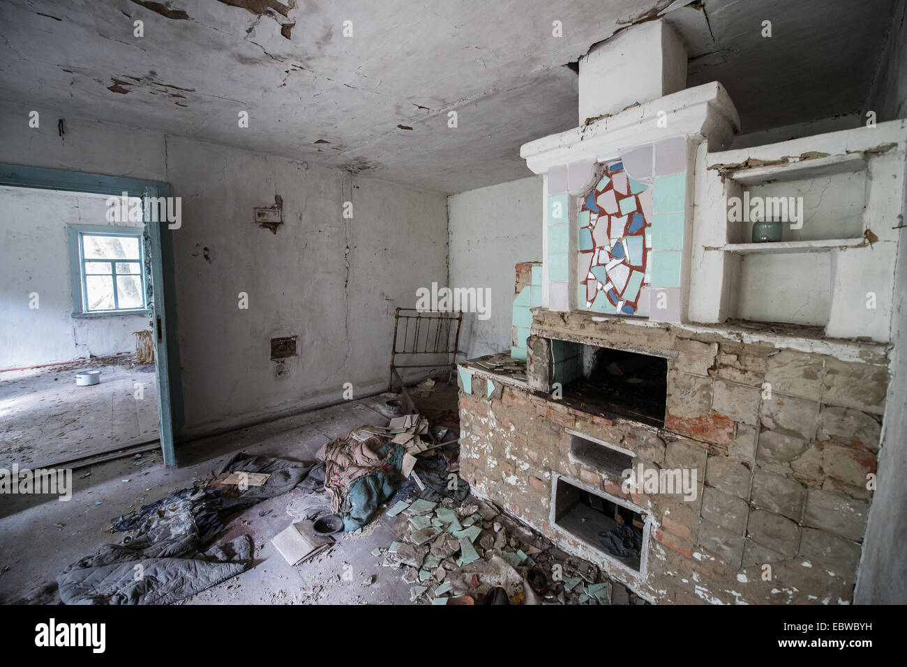 big stove with bedspace in old wooden cottage in abandoned Stechanka village, Chernobyl Exclusion Zone, Ukraine - Stock Image