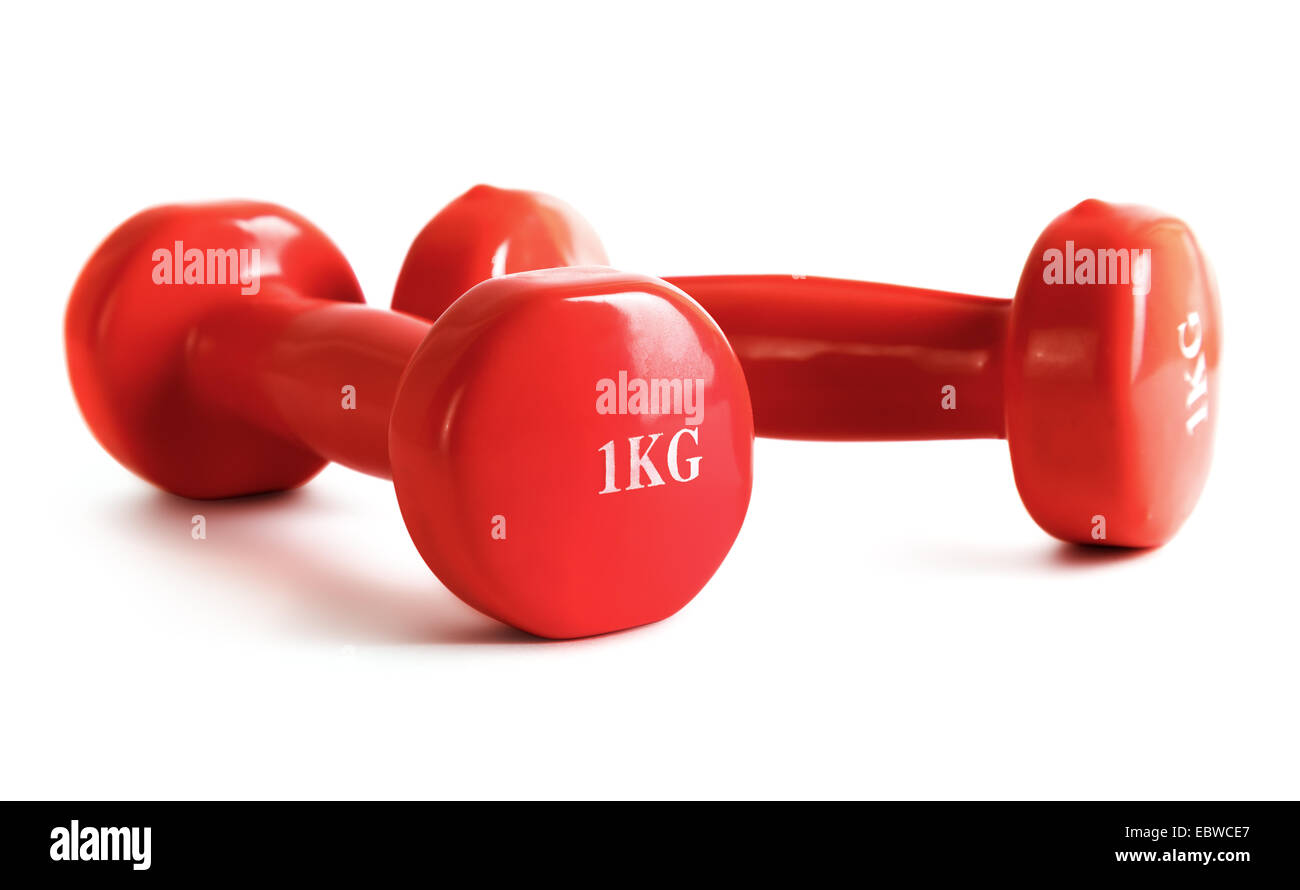 Red dumbbell on a white background. Shallow depth of field. - Stock Image