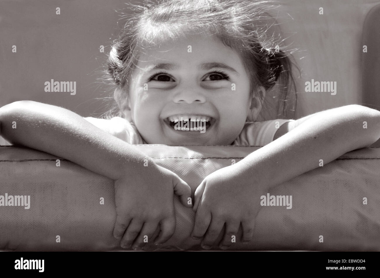 Happy little girl (age 04) ride on thrill ride in amusement park. - Stock Image