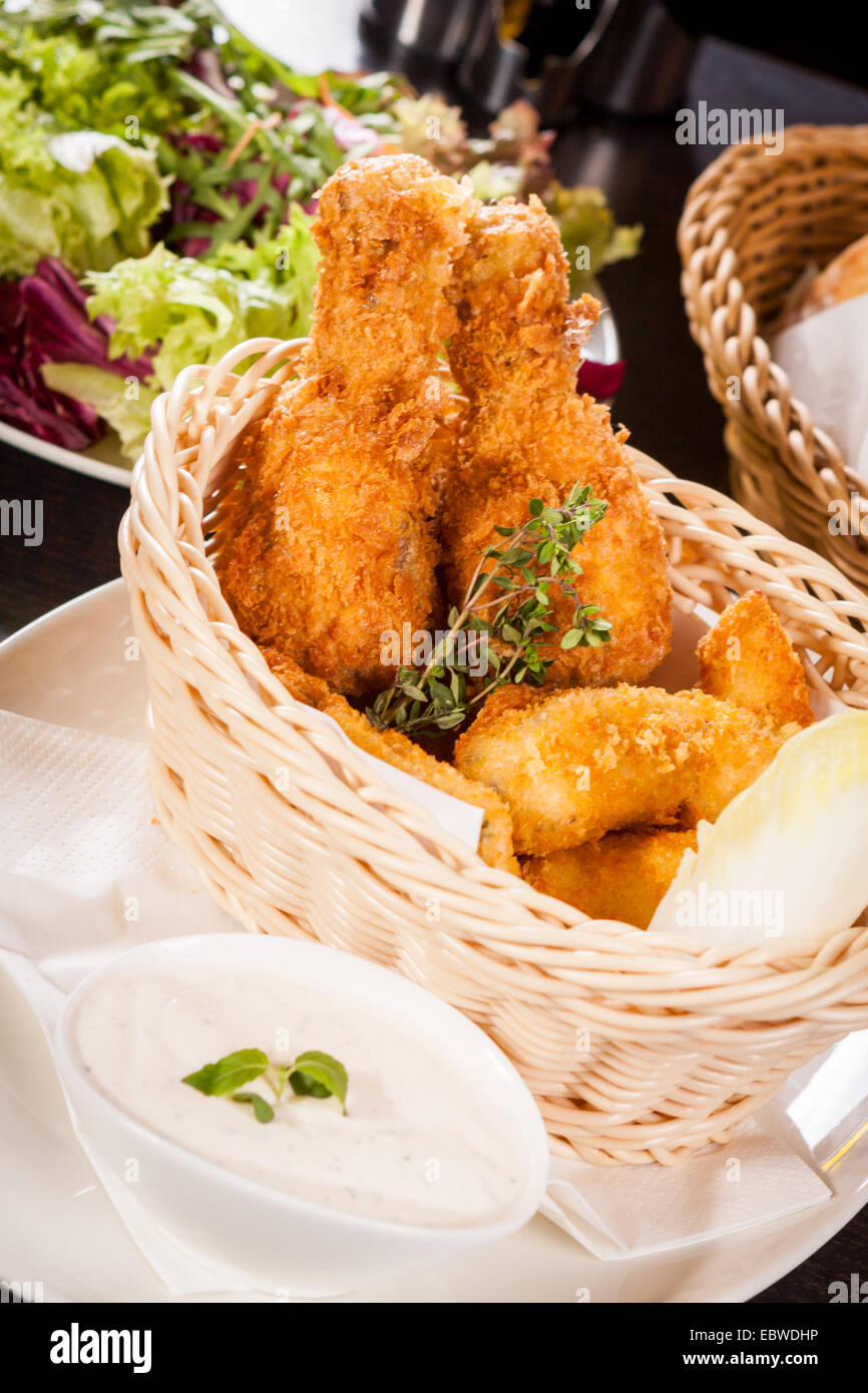Crisp crunchy golden chicken legs and wings deep fried in bread crumbs and served with a bowl of dip in a wicker Stock Photo