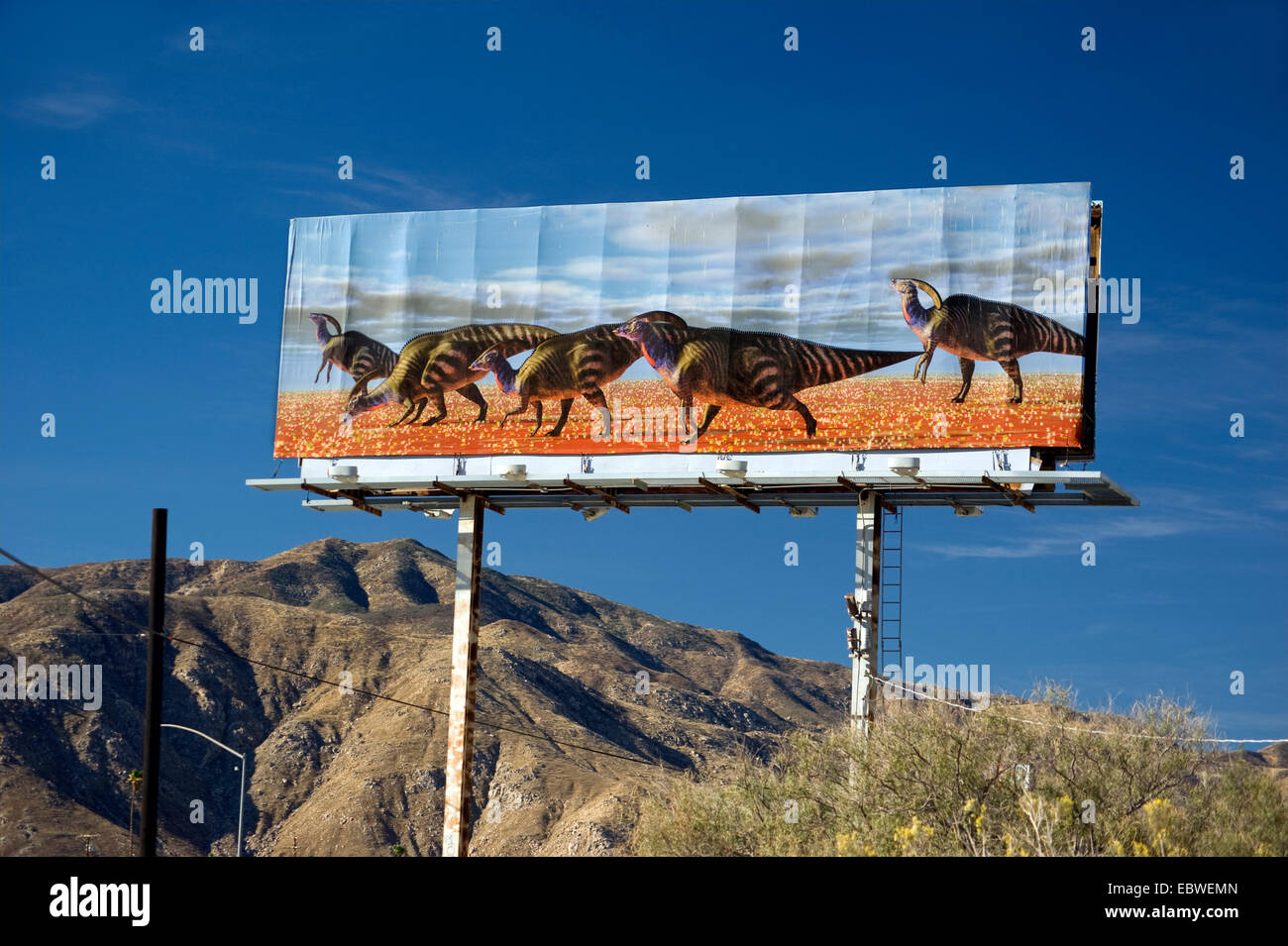 Billboard depicting dinosaurs in desert near Palm Springs, California - Stock Image
