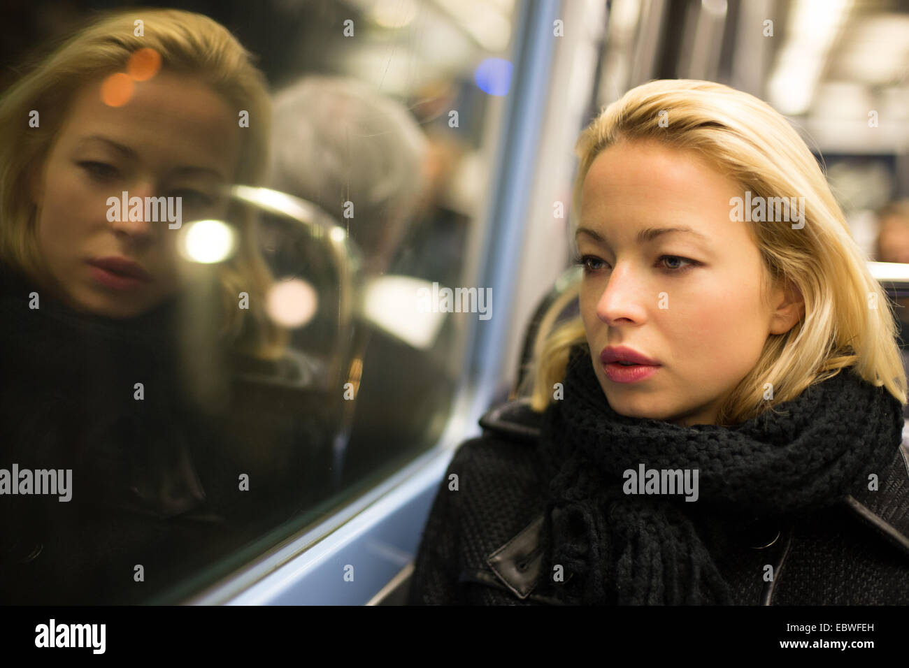 Woman looking out metro's window. - Stock Image