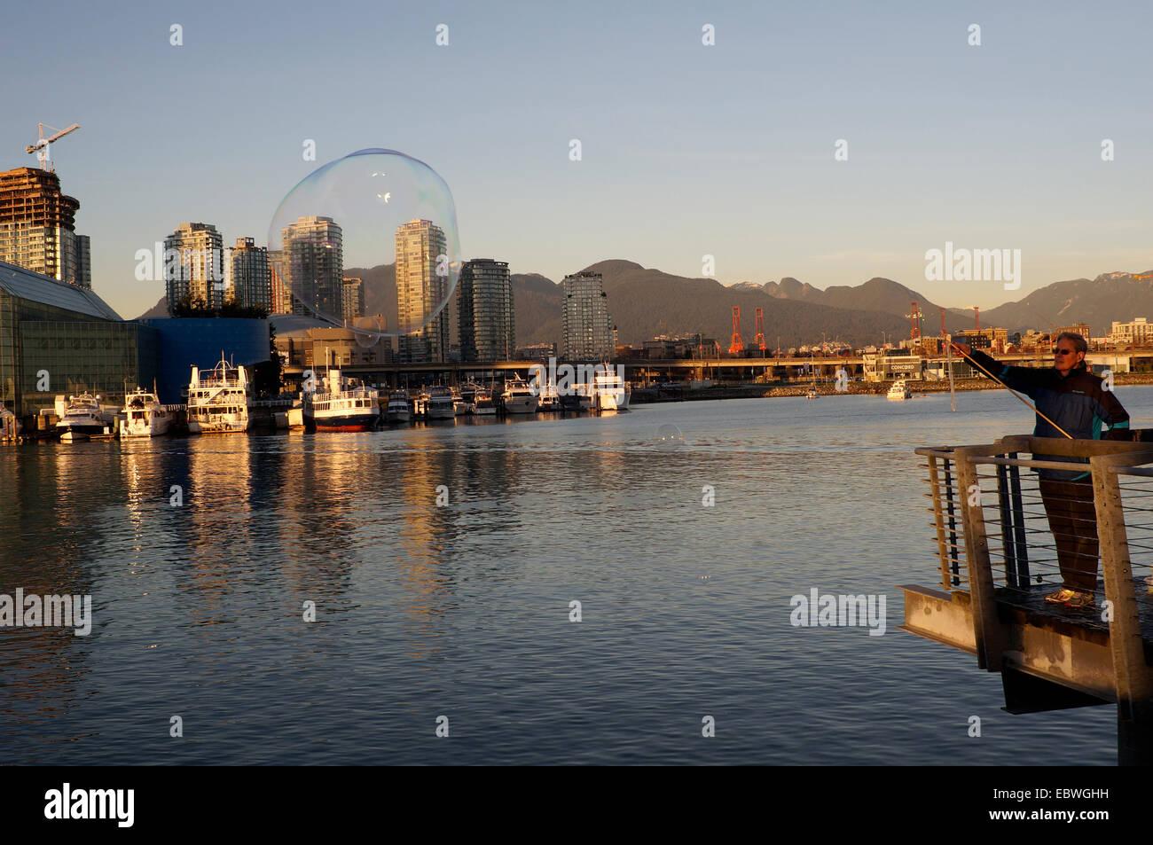 Man making giant soap bubbles, False Creek, Vancouver, British Columbia, Canada - Stock Image