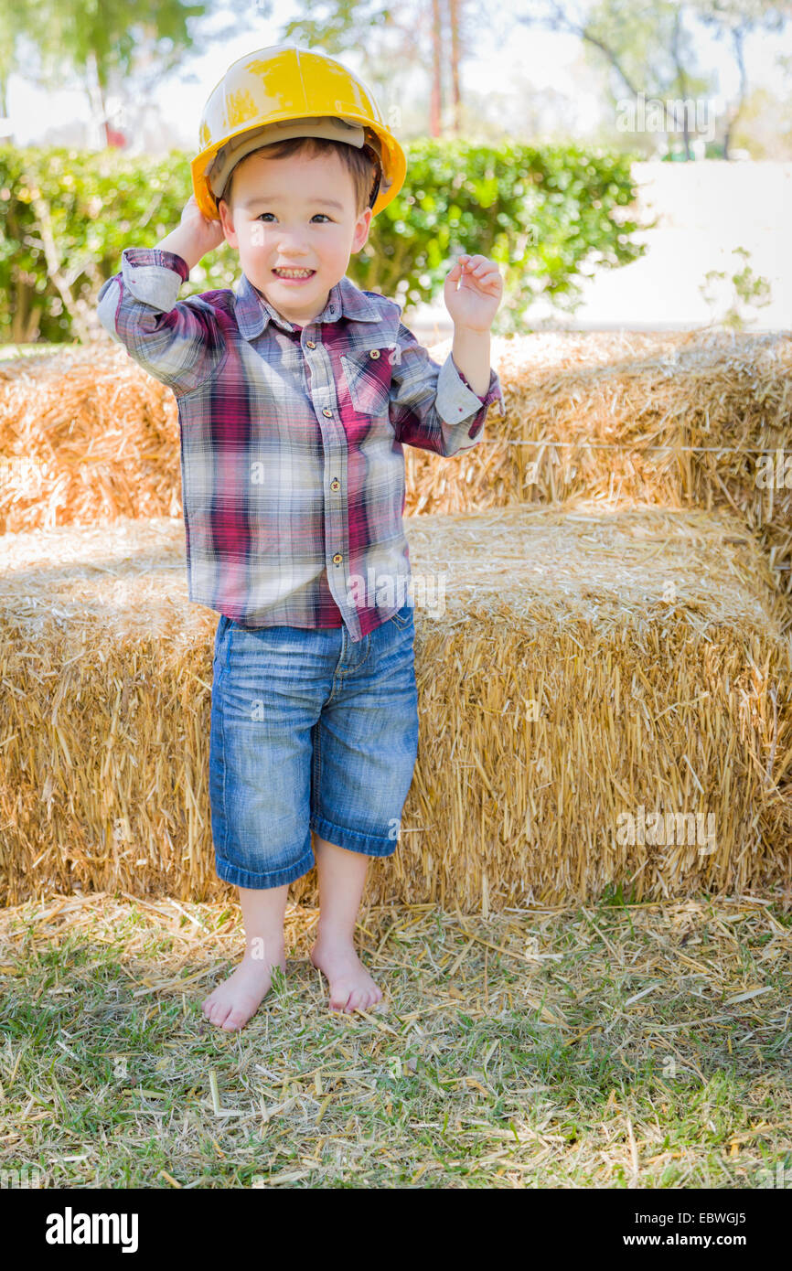 Cute Young Mixed Race Boy Laughing with Hard Hat Outside Near Hay Bale. - Stock Image