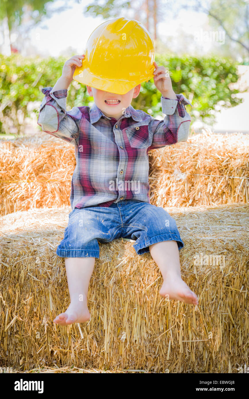 Cute Young Mixed Race Boy Laughing with Hard Hat Outside Sitting on Hay Bale. - Stock Image