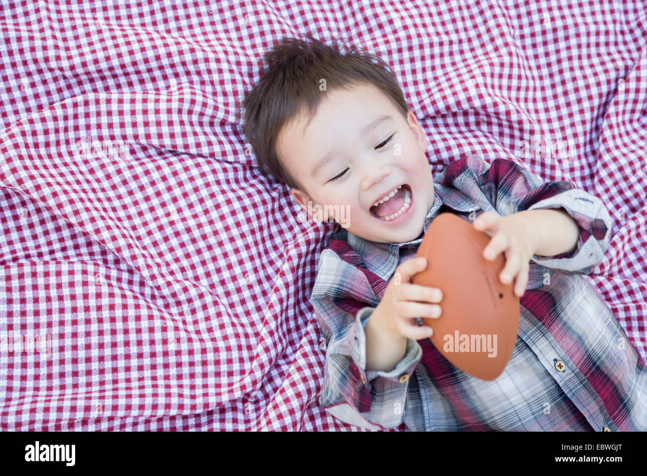 Cute Young Mixed Race Boy Playing With Football Outside On Picnic Blanket. Stock Photo