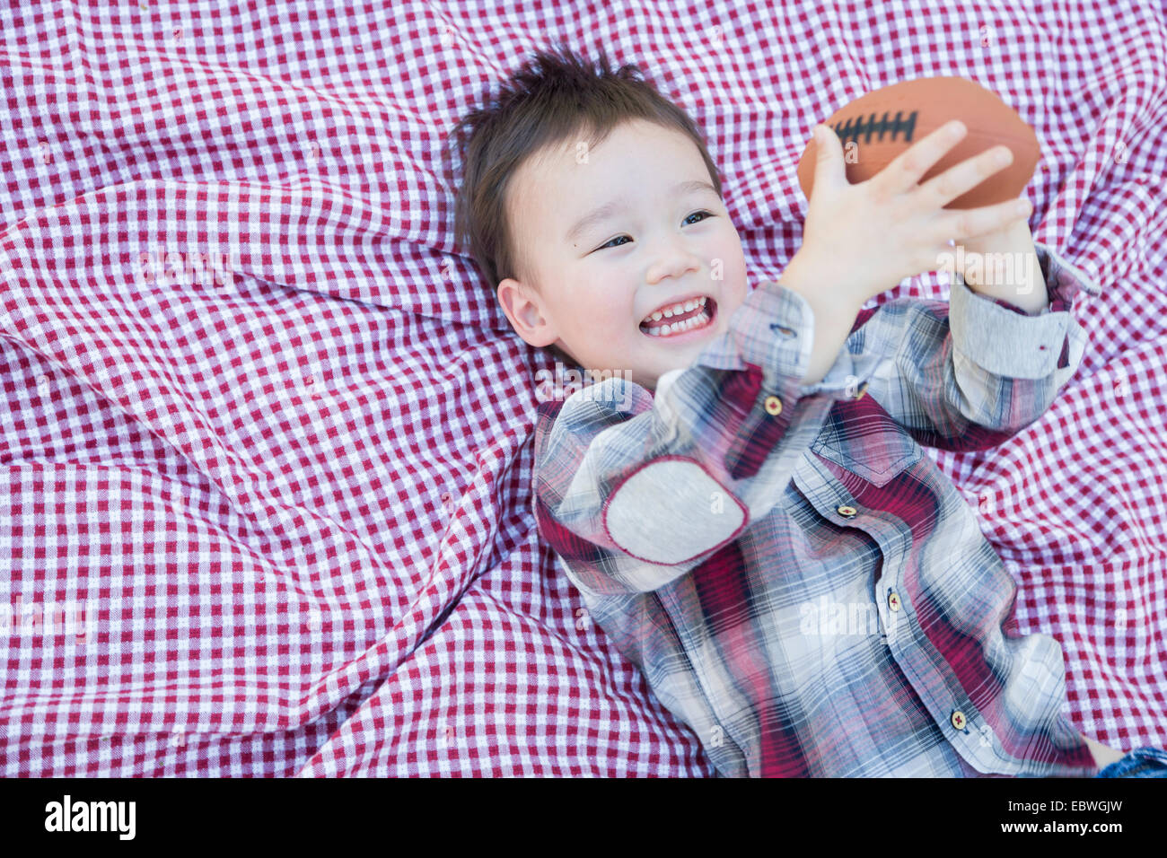 Cute Young Mixed Race Boy Playing With Football Outside On Picnic Blanket. - Stock Image