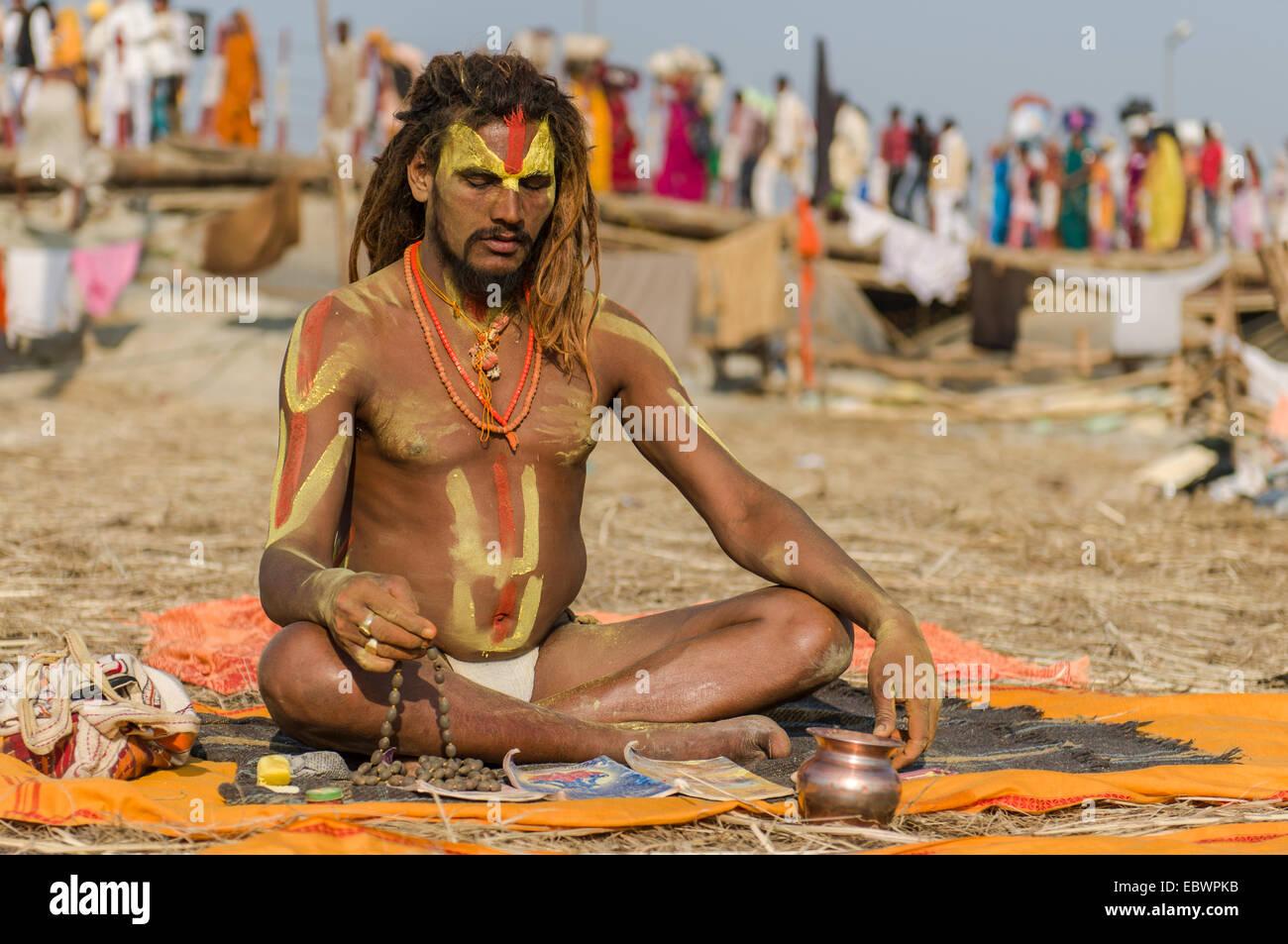 Shiva sadhu, holy man, meditating at the Sangam, the confluence of the rivers Ganges, Yamuna and Saraswati - Stock Image