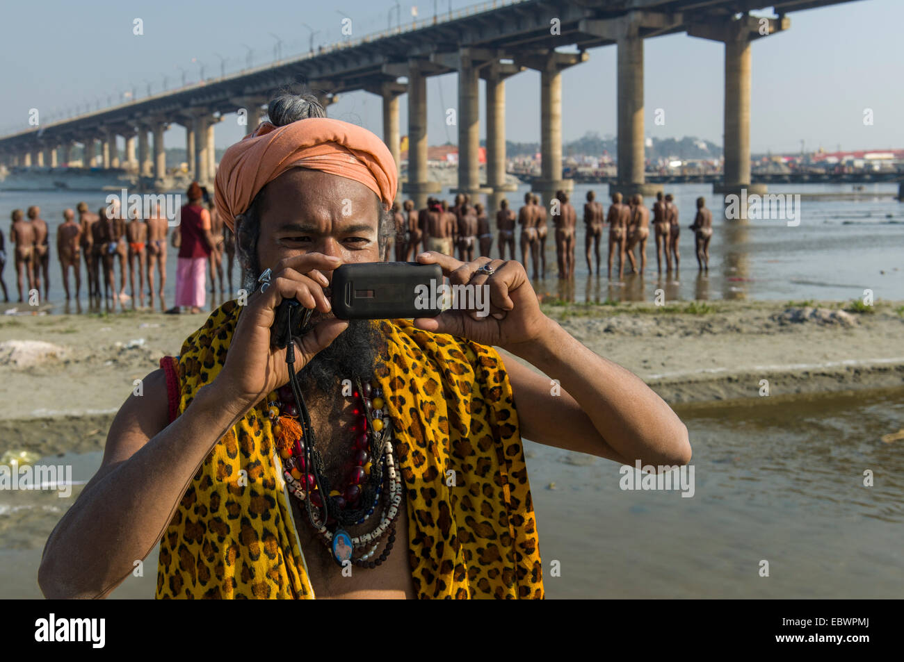 Shiva sadhu, holy man, taking a photograph with his mobile phone at the Sangam, the confluence of the rivers Ganges - Stock Image